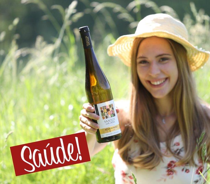 Junge Frau im Gras mit Weiss-Weinflasche