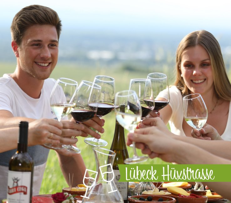 Zwei Gäste einer Weinprobe prosten sich zu